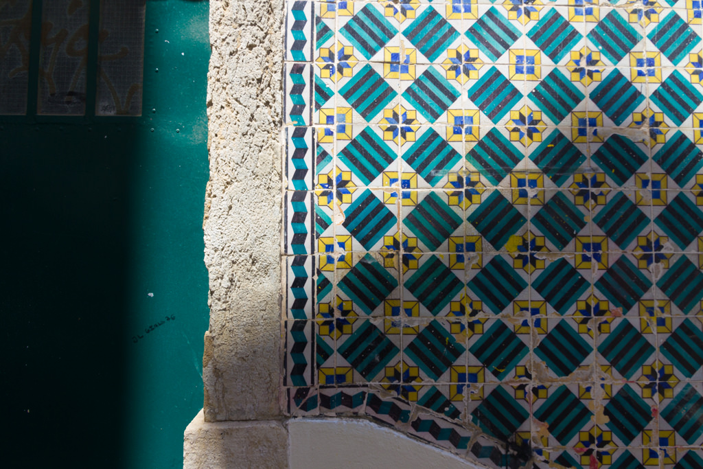Building in Lisbon with colorful green and yellow tiles