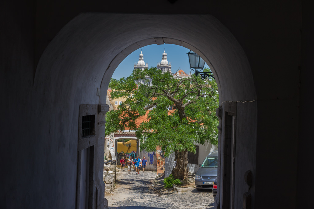 View through an alley with Lisbon's Church of São Vicente of Fora in the background