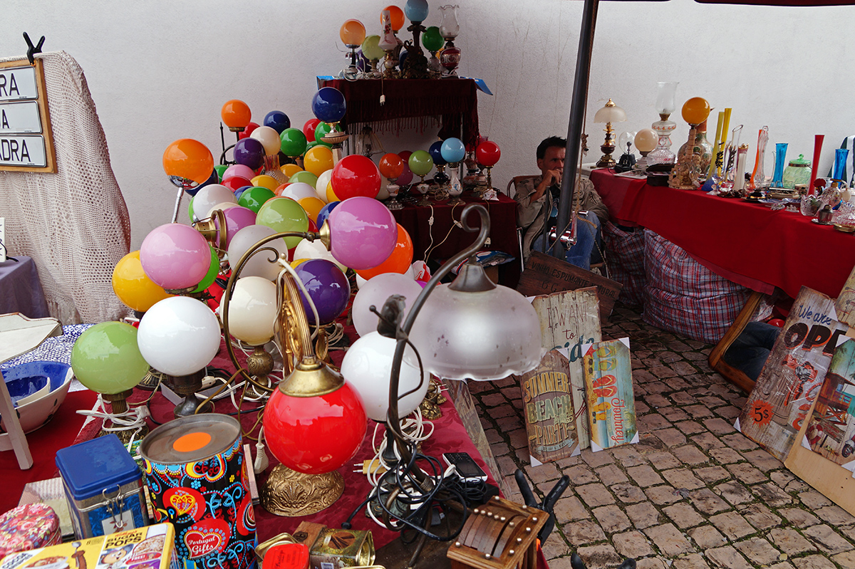 A man selling vintage lamps and other wares at Feira da Ladra market
