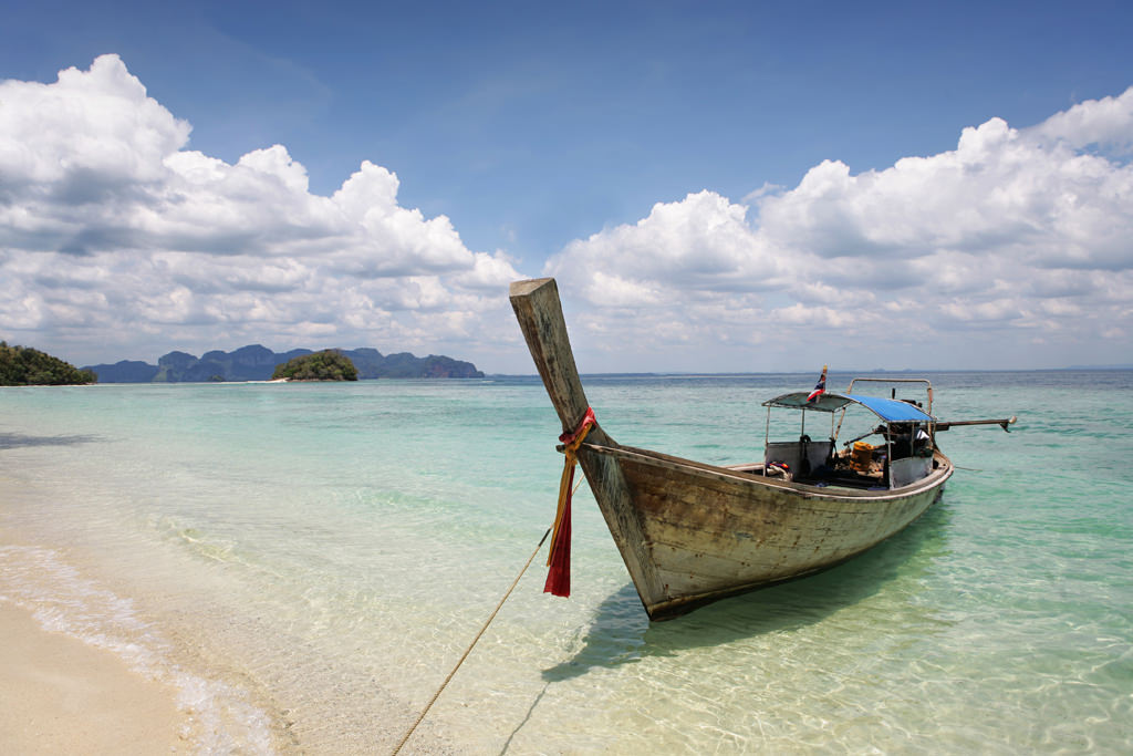 Longtail boat moored on a sunny beach in Thailand